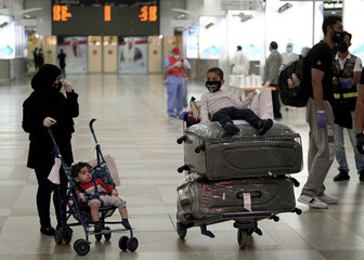 A Kuwaiti family repatriated from Amman, wearing protective face masks, prepare their luggage while arriving at Kuwait Airport, in Kuwait City