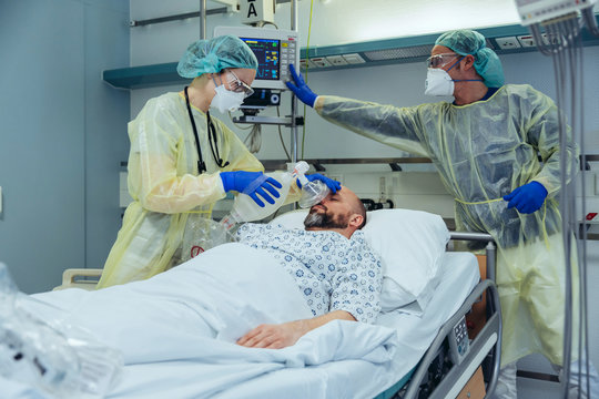 Doctors with bag valve mask caring for patient in emergency care unit of a hospital