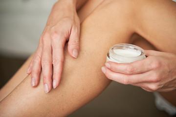 Close-up of woman applying skin cream on her leg