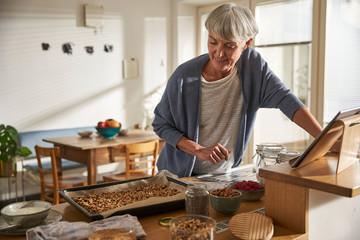 Senior woman preparing granola in kitchen Fotobehang