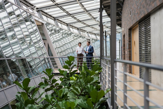 Businessman and woman talking in sustainable office building, using digital tablet