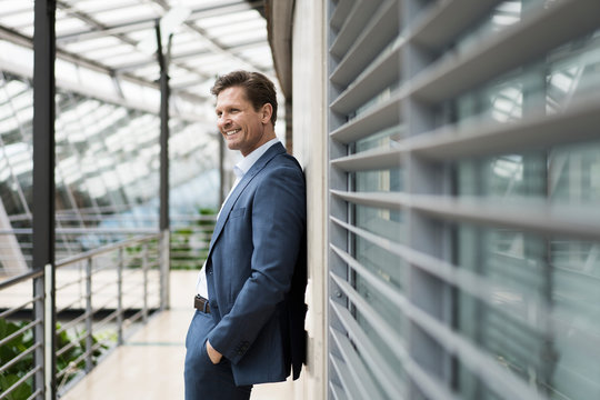 Relaxed businessman leaning aganist wall on gallery of atrium