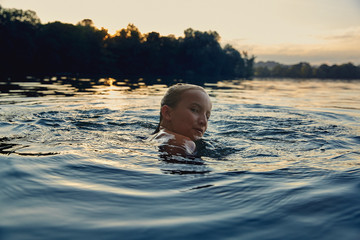 Girl swimming in a lake at evening twilight