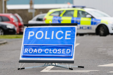 Police road closed sign with police car blocking the road