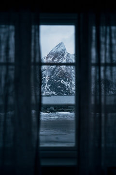 View out of window to coastal landscape with mountain, Lofoten, Norway