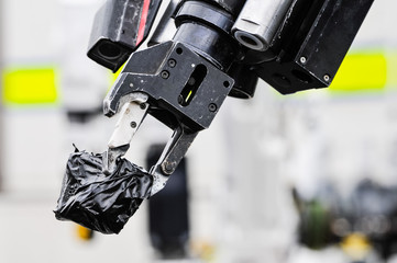 Pincer grip of an army bomb disposal robot holds a suspect object wrapped in tape