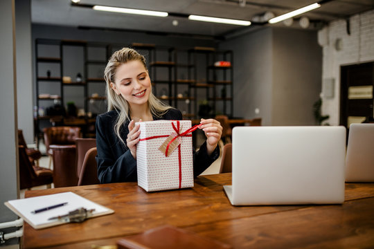 A beautiful blonde businesswoman sits at a Desk in the office and holds a gift that was given by colleagues at work