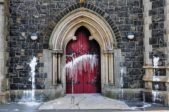 The door of a Roman Catholic Church suffers scorch damage from petrol bombs and paint during a sectarian attack