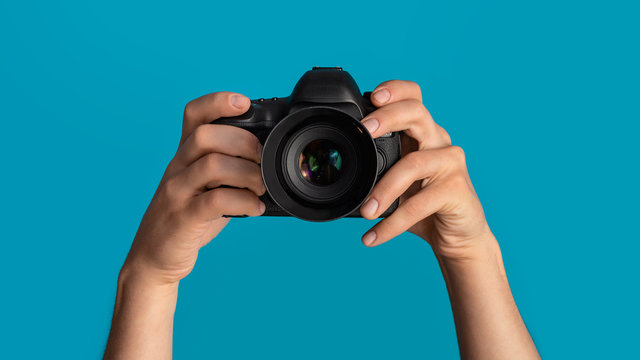 Closeup of photographer pointing DSLR camera at screen, blue background. Panorama