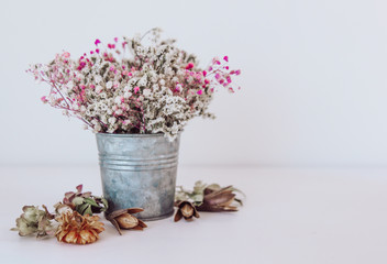 Dried flowers in a rustic iron bucket. Flower composition boho style.