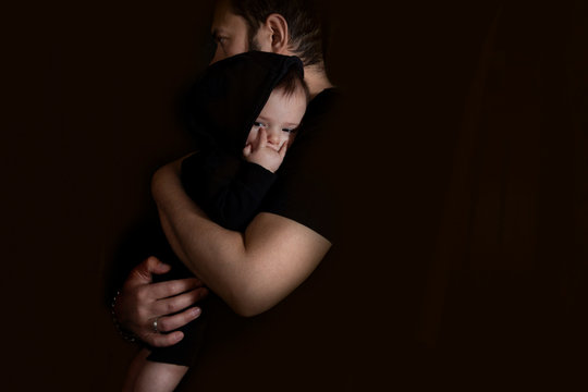 Father hugging and holding his baby in arms on the black background. Baby with horn hand - Hard Rock symbol.