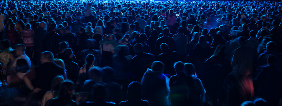 silhouettes of concert crowd in front of bright stage lights.