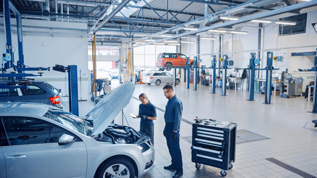 Two Mechanics in a Service are Inspecting a Car After They Got the Diagnostics Results. Female Specialist is Comparing the Data on a Tablet Computer. Repairman is Using a Ratchet to Repair the Faults.