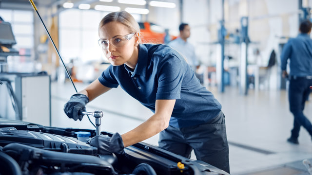 Beautiful Empowering Female Mechanic is Working on a Car in a Car Service. Woman in Safety Glasses is Fixing the Engine. She's Using a Ratchet. Modern Clean Workshop with Cars.