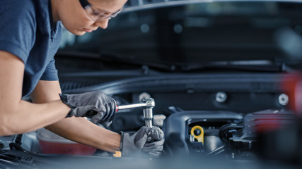 Portrait Shot of a Female Mechanic Working on a Vehicle in a Car Service. Empowering Woman Fixing the Engine. She is Wearing Gloves and Using a Ratchet. Modern Clean Workshop.