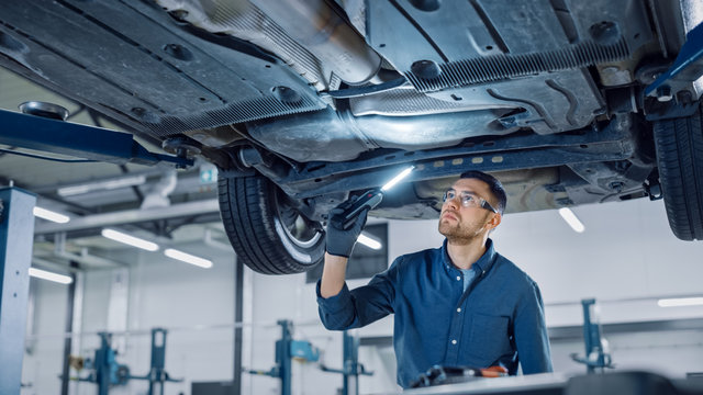Handsome Professional Car Mechanic is Investigating Rust Under a Vehicle on a Lift in Service. Repairman is Using a LED lamp and Walks Towards. Specialist is Wearing Safety Glasses. Modern Workshop.