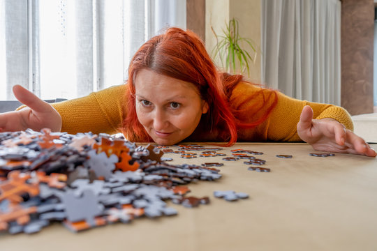 Beautiful redhead woman in a yellow sweater doing a puzzle in the living room at home