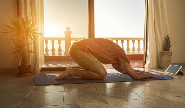 Young man doing yoga at home - Man doing streching yoga exercise indoor at sunset - Yoga at home in time of covid 19 or coronavirus - Healthy lifestyle , mindfulness and balance