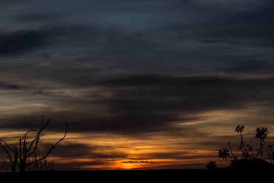 Ciel orange, jaune et gris avec des nuages au couché du soleil