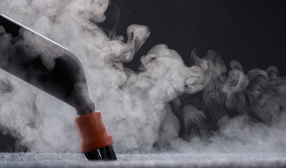 Steam close-up. Steam carpet cleaning on a grey background. Home cleaning.
