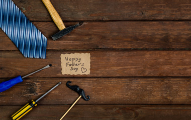 Happy Fathers Day gift box with tie, hammer, blue box and mustache on a rustic wood background.