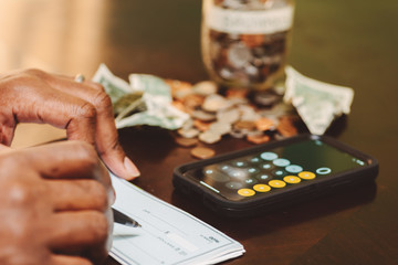 african american  man at the table calculating how much he needs to tap into his savings or rainy day funds
