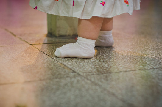 Low Section Of Baby Girl Standing On Tiled Floor