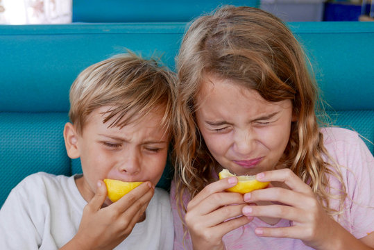 Boy and girl making funny faces as they bite into sour lemons
