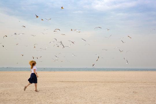 Two children running along the beach scaring birds. Sebastian Inlet State Park, Florida