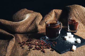 Papiers peints Café en grains black coffee in a transparent glass Cup on a background of burlap. next to sugar, coffee beans and ground coffee. vintage