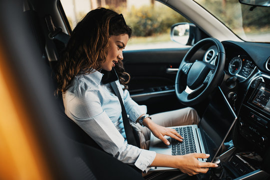 Beautiful young businesswoman driving car and using laptop.