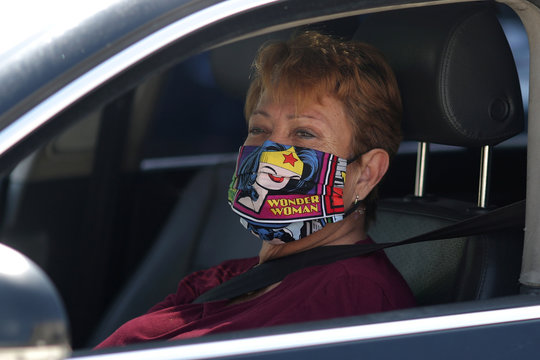 A woman wears a Wonder Woman mask as she waits in line at a Los Angeles Food Bank drive-through food giveaway as the global outbreak of coronavirus disease (COVID-19) continues, in Los Angeles