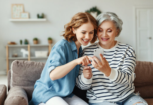 Cheerful mother and daughter using smartphone on sofa.