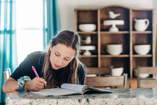 Teenage girl with long hair and scrunchie on her wrist studying and working on homework at the kitchen countertop bar area with a window and curtains. Stay home education middle school junior high