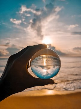 Cropped Hand Holding Crystal Ball At Beach Against Sky During Sunset