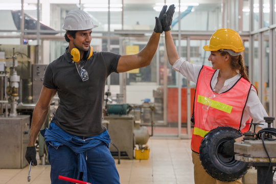 two factory workers having highfive together showing teamwork of success in metal work factory