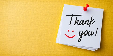 White Sticky Note With Thank You And Red Push Pin On Yellow Background