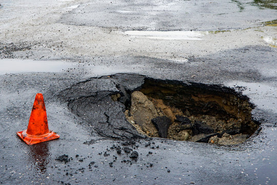 huge pit hole on the road, failure in the asphalt, marked with an orange cone, dangerous for travel, earthquake, ground movement