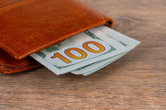 100 dollars banknotes with orange wallet on wooden table. Pension or unemployment benefit concept.