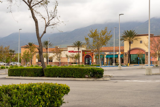 Fontana, CA / USA – April 19, 2020:  An empty parking lot at the Falcon Ridge Town Center located in Fontana, California, with retail businesses temporarily closure due to the COVID-19 crisis.