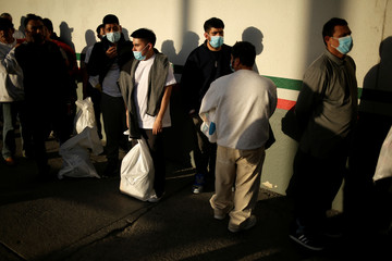 Mexican immigrants wait outside of a National Institute of Migration (INM) building after being deported from the United States and crossing the Paso del Norte border bridge amid the spread of the coronavirus disease (COVID-19), in Ciudad Juarez
