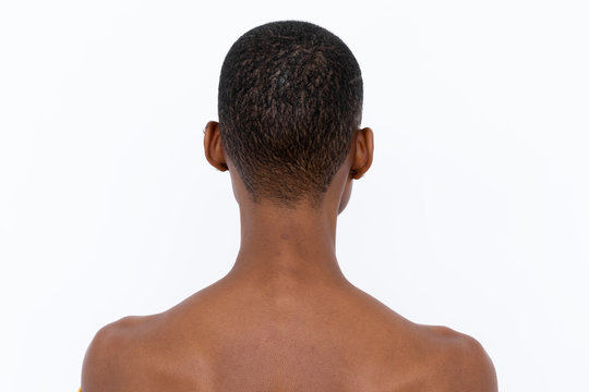 Black woman with shaved head facing the wall
