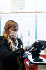 Woman in a face mask wearing latex gloves while purchasing at a self-checkout in a supermarket...