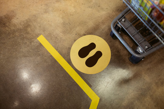 Supermarket social distancing sign on the ground during coronavirus pandemic