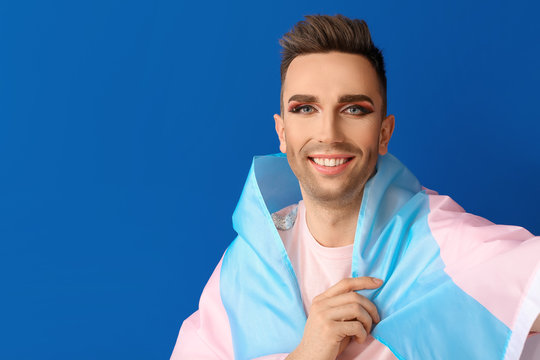 Portrait of young transgender woman with flag on color background