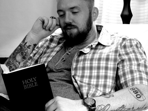 Man Reading Bible While Sitting At Home