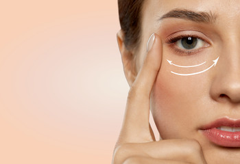 Obraz beauty, makeup and lifting concept - close up of beautiful young woman face with arrows under eye area over beige background - fototapety do salonu