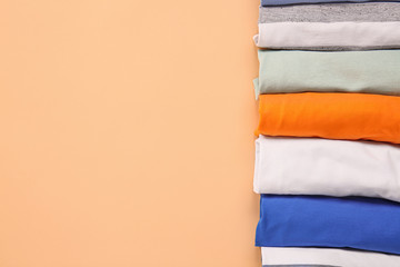 Stylish t-shirts on color background