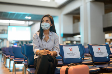 Young Asian tourist woman with mask thinking and sitting with distance at the airport