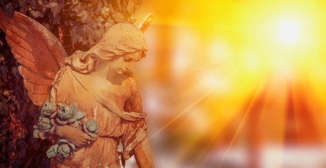 Fototapete - Angel in sunlight as a symbol of strength, truth and faith. Ancient stone statue.